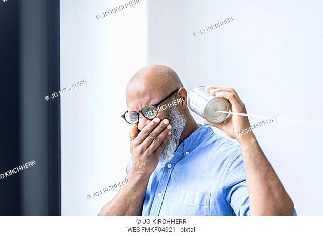 Laughing businessman with tin can phone in the office