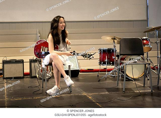 Teen Girl Playing Electric Guitar on Stage