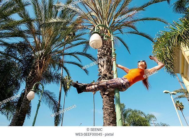 USA, California, Los Angeles, Marina Del Rey, Sporty woman on a lamp post, poledance