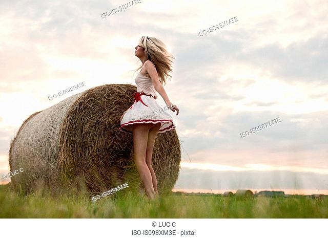Young woman dancing by hay bale in field