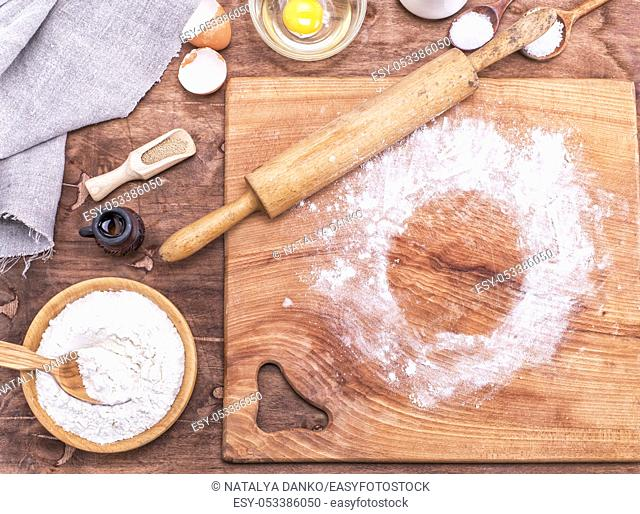 square wooden kitchen board with rolling pin and wheat flour in a wooden bowl, top view