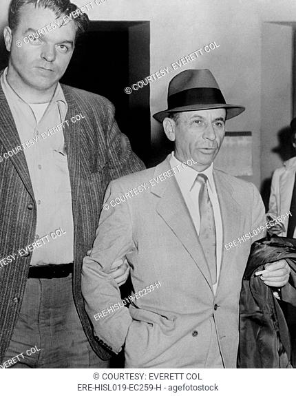 Gambling boss Meyer Lansky 1902-1983, led by a detective for booking on vagrancy charge at 54th Street police station, New York City, February 13, 1958