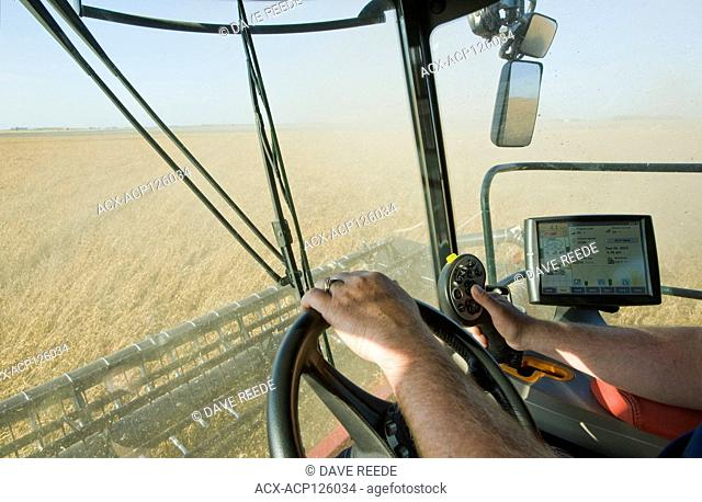 a farmer operates the controls of his combine during the soybean harvest, near Dugald, Manitoba, Canada