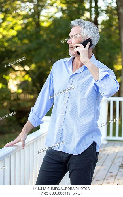 Gray-haired man making phone call while standing outdoors on porch, Orleans, Massachusetts, USA
