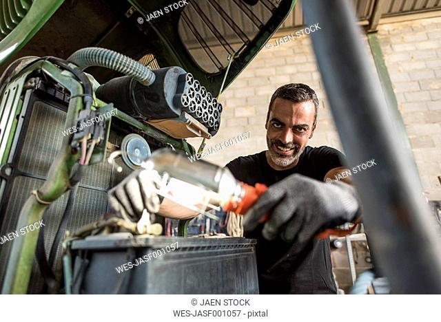 Smiling mechanic repairing tractor