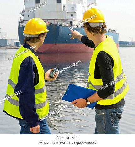 Two dockers talking about a large oil tanker, one with a cb radio, and the other pointing at the industrial vessel with a clip board in his hand