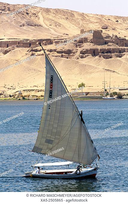 Felucca sailing the Nile River, Tombs of the Nobles (background), Aswan, Egypt