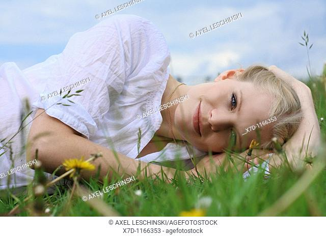 Portrait of young blonde woman lying on meadow