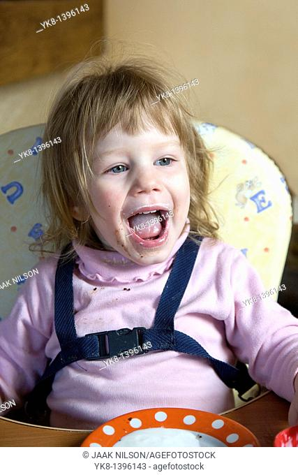Happy Dirty Two Year Old Caucasian Kid Girl Sitting and Shouting in High Chair