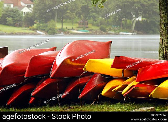 Red and yellow canoes are stacked on top of each other at a park in Connecticut