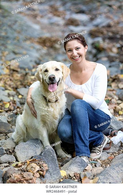 Woman sitting in the forest with Labrador