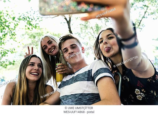 Group of happy friends taking a selfie outdoors