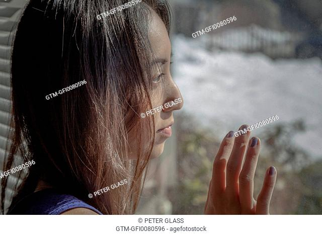 Young Asian woman looking out her window