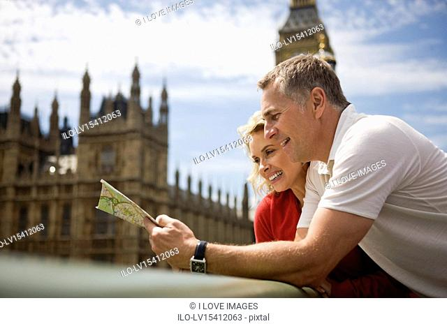 A middle-aged couple standing near the Houses of Parliament, looking at a map