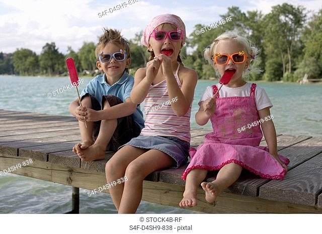 Three children with sunglasses each eating an ice lolly , close-up