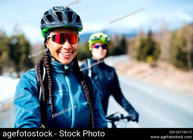 Two mountain bikers riding on road outdoors in winter, looking at camera