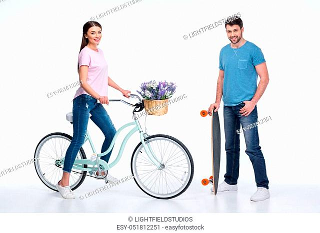 smiling couple with skateboard and bicycle on white