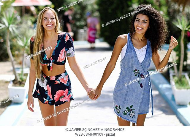 Portrait of two happy young women holding hands in summer