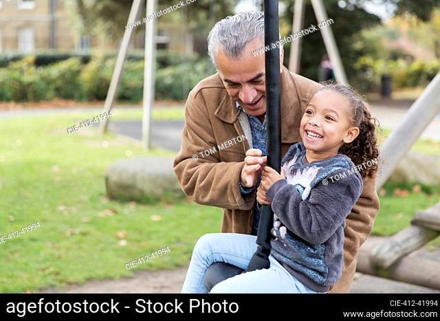 Happy grandfather and granddaughter playing at playground
