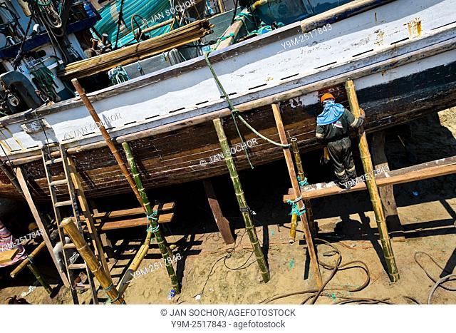 An Ecuadorian shipbuilding worker repairs the shell of a traditional wooden fishing vessel in an artisanal shipyard on the beach in Manta, Ecuador
