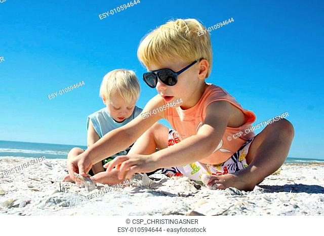 Two Children Playing in the Sand at the Beach