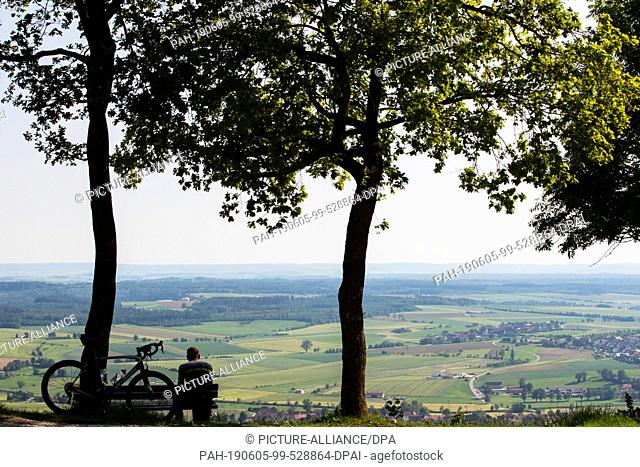 05 June 2019, Bavaria, Gerolfingen: A cyclist sits on a bench and looks down from Hesselberg into the valley. Hesselberg is the highest elevation in Middle...