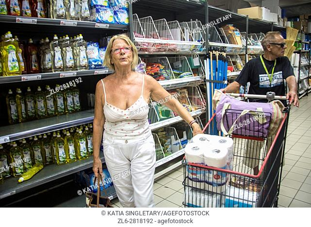 Mature retired senor caucasian woman doing her grocery shopping on vacation while her husband push the cart