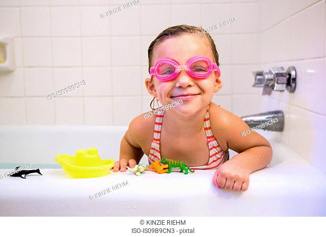 Portrait of girl wearing swimming goggles in bath, looking at camera smiling