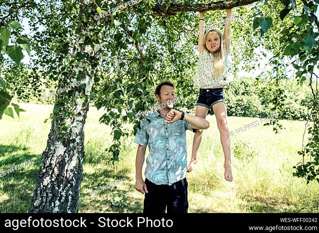 Father checking the time with daughter hanging on a branch of a birch tree