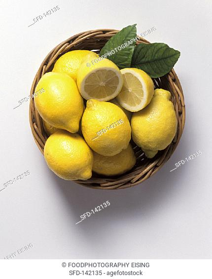 Lemons in basketwork bowl, one halved