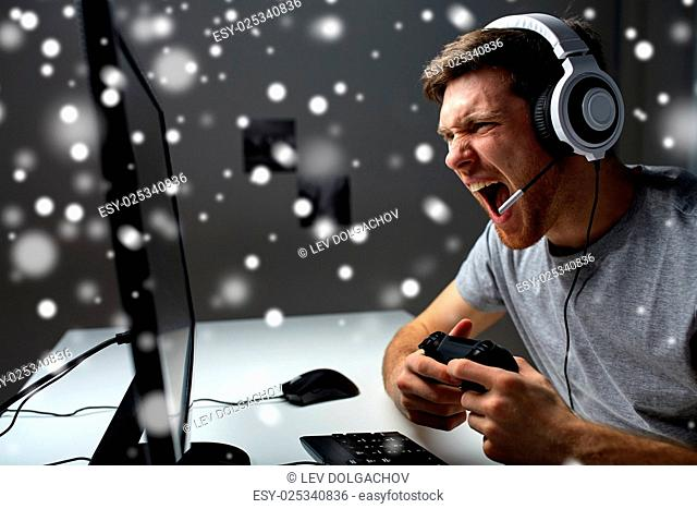 technology, gaming, entertainment, let's play and people concept - screaming man in headset with controller gamepad playing computer game at home and streaming...