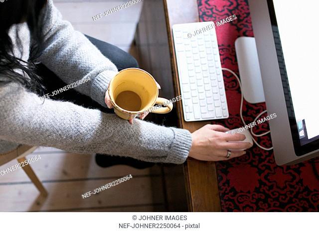 Woman holding mug, using computer