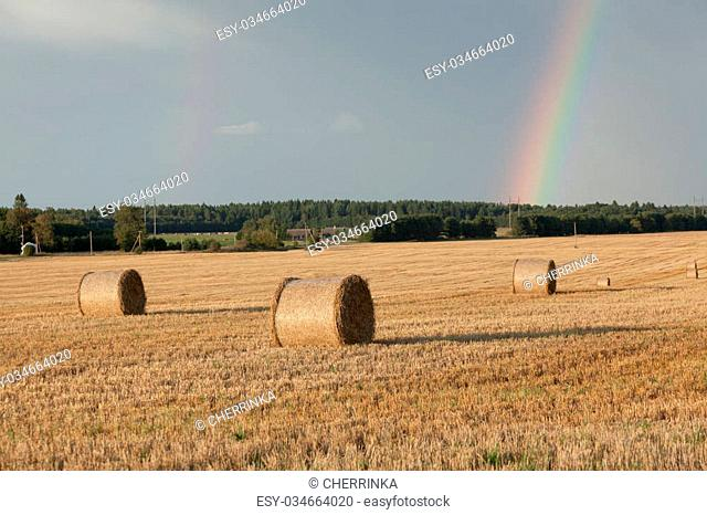 Straw bales landscape with rainbow on a sunny day