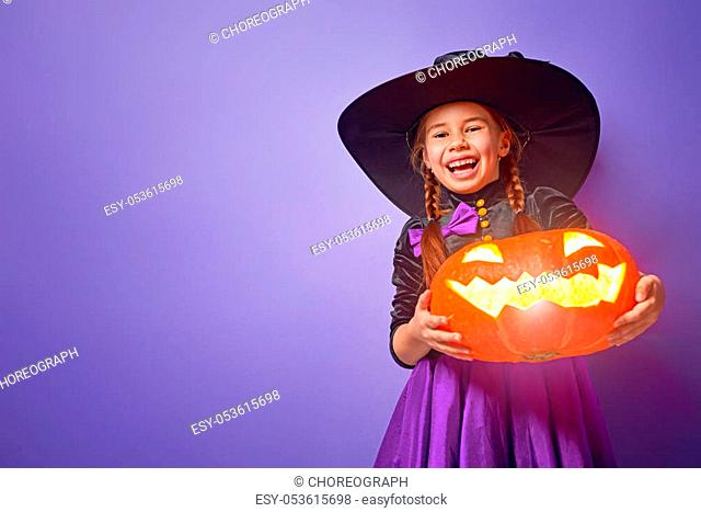 Happy Halloween! Cute little witch with a pumpkin
