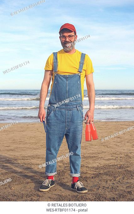 Portrait of smiling man in dungarees standing on the beach holding bottles of soft drinks