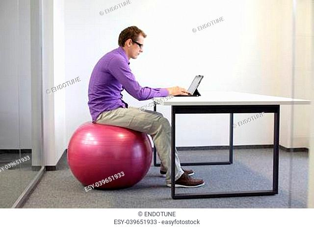 bad sitting posture at tablet - business man on stability ball in his office
