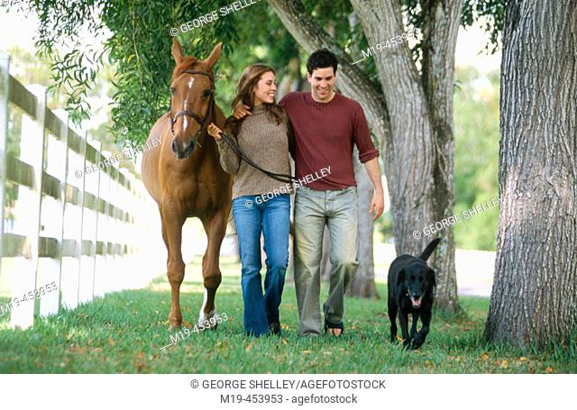 couple walking with a dog and their horse