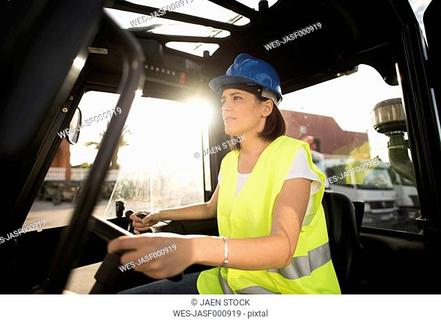 Female construction worker driving forklift