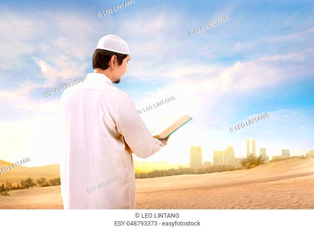 Rear view of asian muslim man with cap standing and reading the quran on the sand with blue sky background