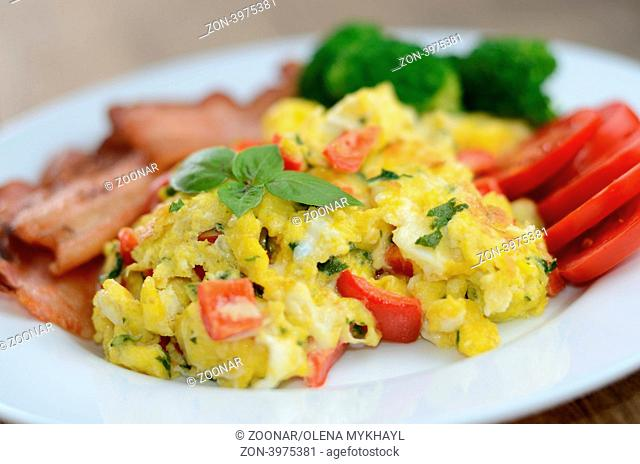 Scrambled eggs with fried bacon on the white plate