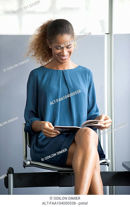 Woman reading in waiting room, smiling cheerfully