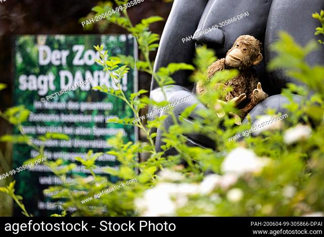 """04 June 2020, North Rhine-Westphalia, Krefeld: A small stuffed monkey lies in the arms of a monkey sculpture - next to it a sign saying """"""""The zoo says thank you"""