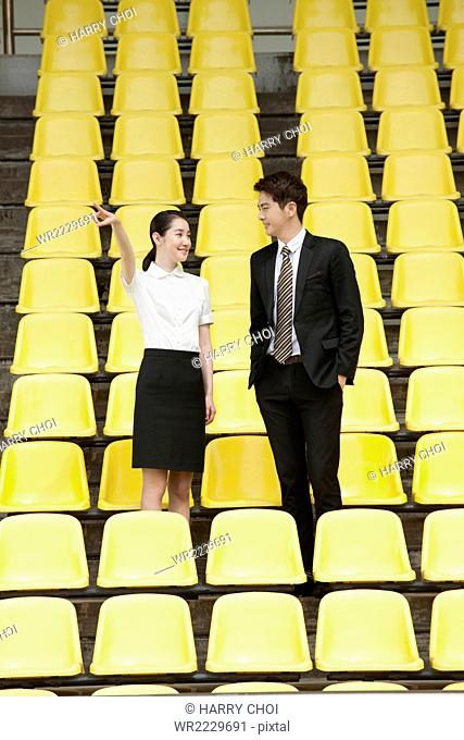 Businessman and busiensswoman standing and pointing face to face at stadium seats