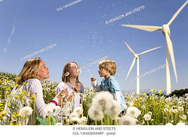 Girl and boy and mother at wind turbines