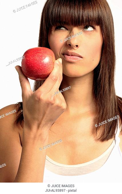 Woman holding apple and making a face