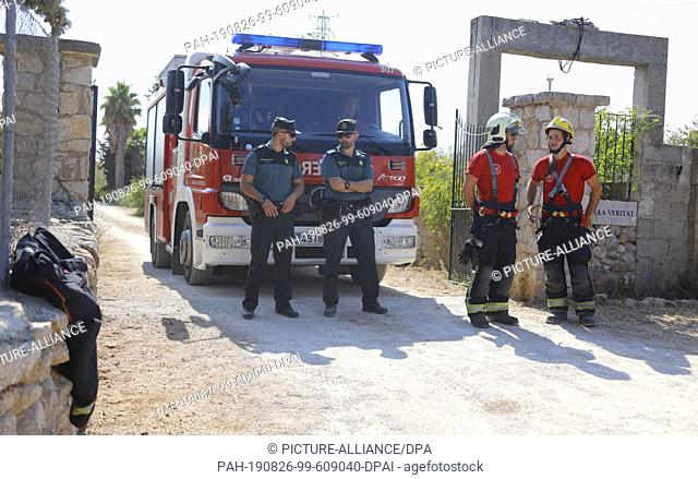 """25 August 2019, Spain, Inca: Members of the """"""""Guardia Civil"""""""" police unit (l) and the fire brigade are standing near the crash site following a collision..."""