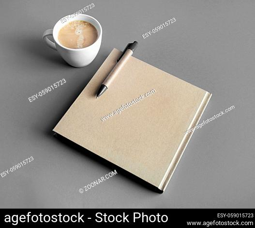 Photo of blank closed brochure, pen and coffee cup on gray paper background. Responsive design mockup. Stationery elements