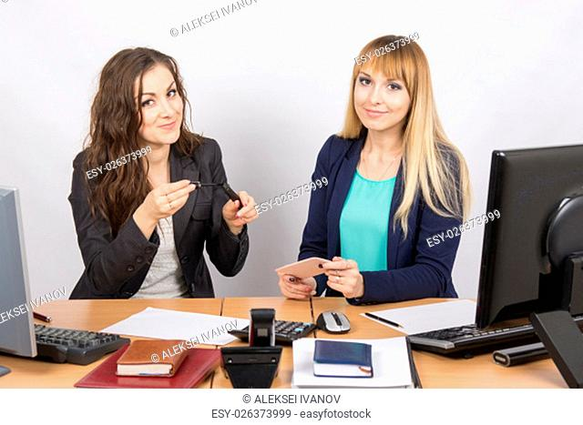 Two young pretty business woman sitting at a office table is divided into two jobs