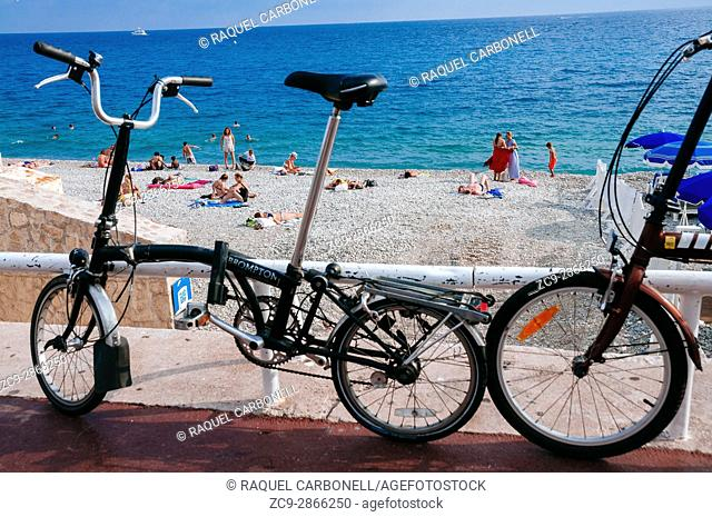 Tourists sunbathing in 'Neptune Plage' stone beach and bikes parked in front. Nice, French Riviera, France