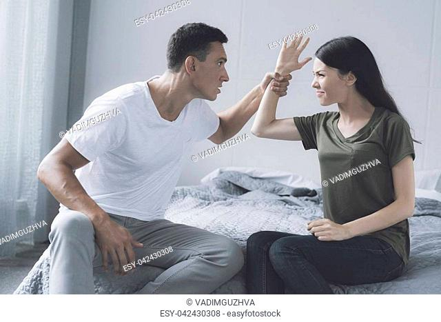 Husband and wife fight. A man sitting on the bed caught the hand of a woman who was sitting by her side and wanted to hit him